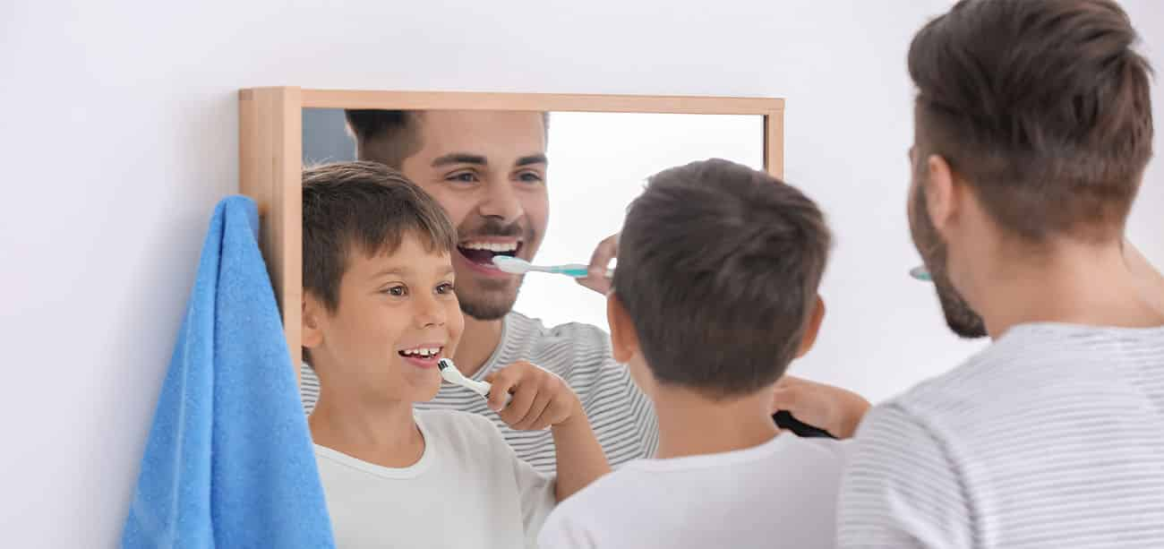 boy and father brushing teeth